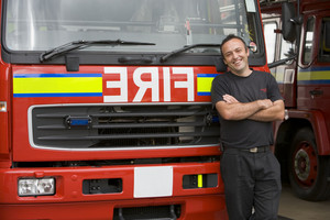 Portrait of a firefighter standing by a fire engine