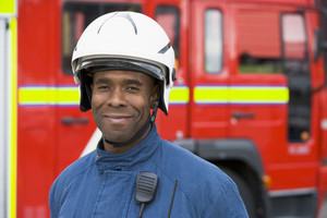 Portrait of a firefighter standing in front of a fire engine