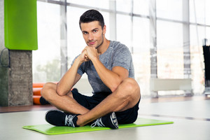 Portrait of a fitness man sitting on yoga mat at gym