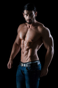 Portrait of a fitness man with muscular body posing on black background