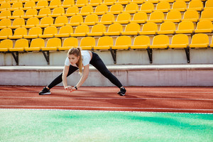 Portrait of a fitness woman doing warm up exercises at stadium