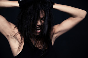 Portrait of a fitness woman screaming over black background