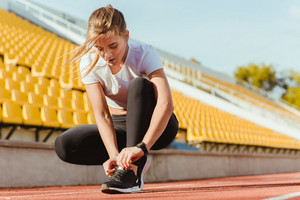 Portrait of a fitness woman tie shoelaces at outdoor stadium