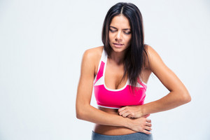 Portrait of a fitness woman with stomach pain over gray background