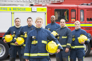Portrait of a group of firefighters by a fire engine