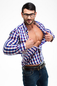 Portrait of a handsome man in glasses unbuttoning shirt isolated on a white background