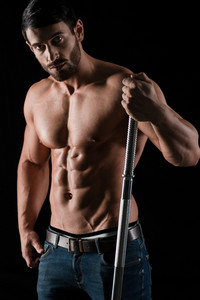 Portrait of a handsome man with muscular body holding barbell on black background