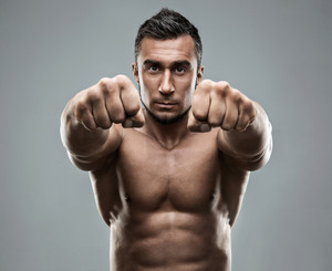 Portrait of a handsome muscular man boxing at camera