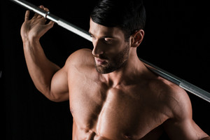 Portrait of a handsome muscular man holding barbell on black background