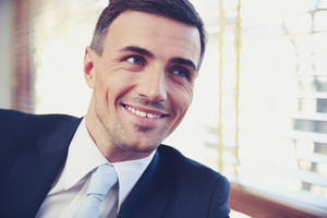 Portrait of a handsome smiling businessman in suit looking away