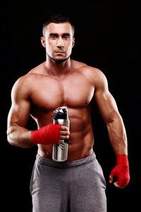 Portrait of a handsome sportsman with bottle over black background