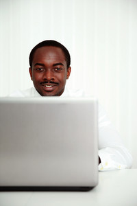 Portrait of a happy african businessman sitting at the table with laptop in office