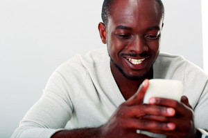Portrait of a happy african man using smartphone