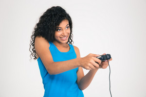 Portrait of a happy afro american woman playing in video game with joystick isolated on a white background