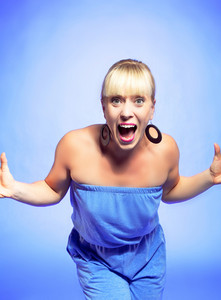 Portrait of a happy and surprised fashionable young woman against a blue background
