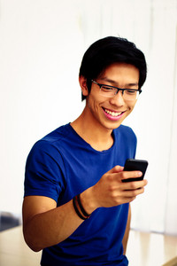 Portrait of a happy asian man standing and using smartphone