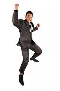 肖像一個幸福的商人在空中跳躍反對孤立的白色背景