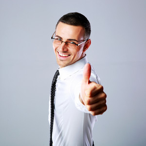 Portrait of a happy businessman showing thumb up over gray background