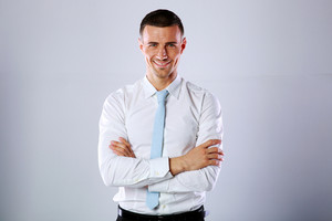 Portrait of a happy businessman standing with arms folded on gray background