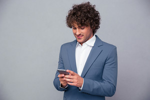 Portrait of a happy businessman using smartphone