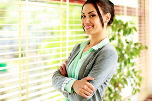Portrait of a happy businesswoman with arms folded standing near window in office