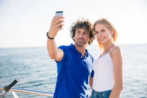 Portrait of a happy couple making selfie photo on smartphone outdoors