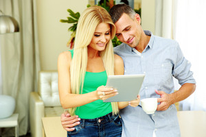 Portrait of a happy couple using tablet computer and holding cup of coffee