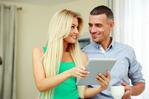 Portrait of a happy couple with tablet computer and cup of coffee