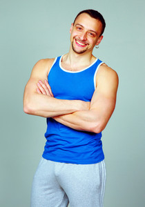 Portrait of a happy sport man with arms folded on gray background
