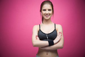 Portrait of a happy sports woman standing with arms folded over pink background