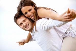 Portrait of a happy young couple having fun against a bright background