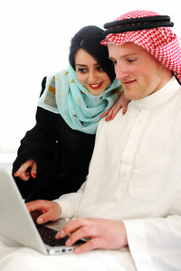 Portrait of a happy young couple sitting on a sofa using laptop