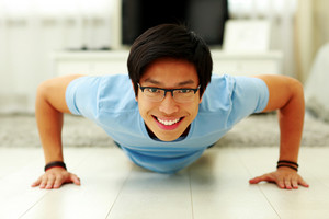 Portrait of a happy young man doing push ups in the living room at home