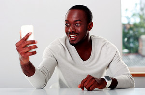 Portrait of a laughing african man looking on smartphone
