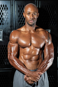 Portrait of a lean toned and ripped muscle fitness man under dramatic low key lighting in the locker room.