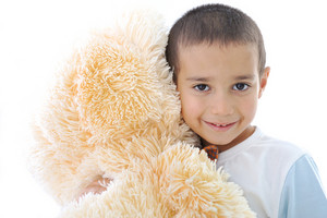 Portrait of a little kid with bear toy isolated in white