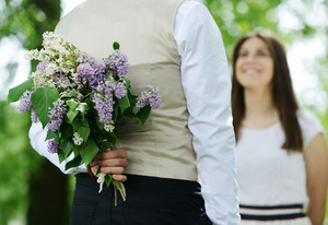 Portrait of a man hiding a flowers bouquet behind his back to surprise to a female