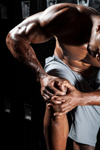 Portrait of a muscle fitness man reaching for his knee in pain