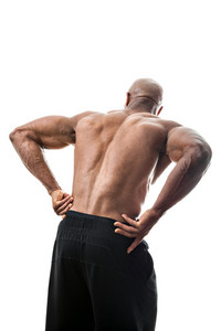 Portrait of a muscle fitness man reaching for his lower back in pain
