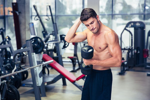 Portrait of a muscular fitness man doing exercises with dumbbell at gym