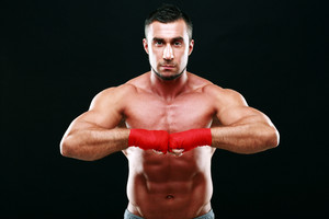 Portrait of a muscular man in red gloves on a black background