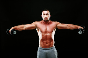 Portrait of a muscular man lifting dumbbells over black background