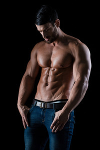 Portrait of a muscular man posing on black background