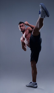 Portrait of a muscular man practicing body combat over gray background