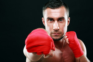 Portrait of a muscular man punching camera on black background