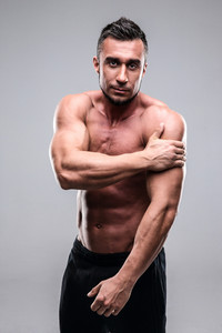 Portrait of a muscular man touching his shoulder