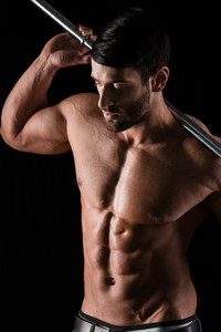 Portrait of a muscular man with naked body workout with barbell on black background