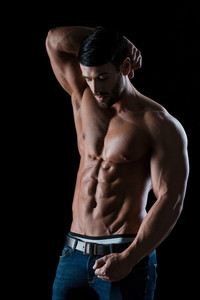 Portrait of a muscular man with naked torso posing on black background