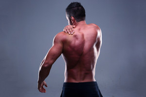Portrait of a muscular mans back over gray background