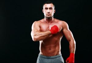 Portrait of a muscular sportsman on black background